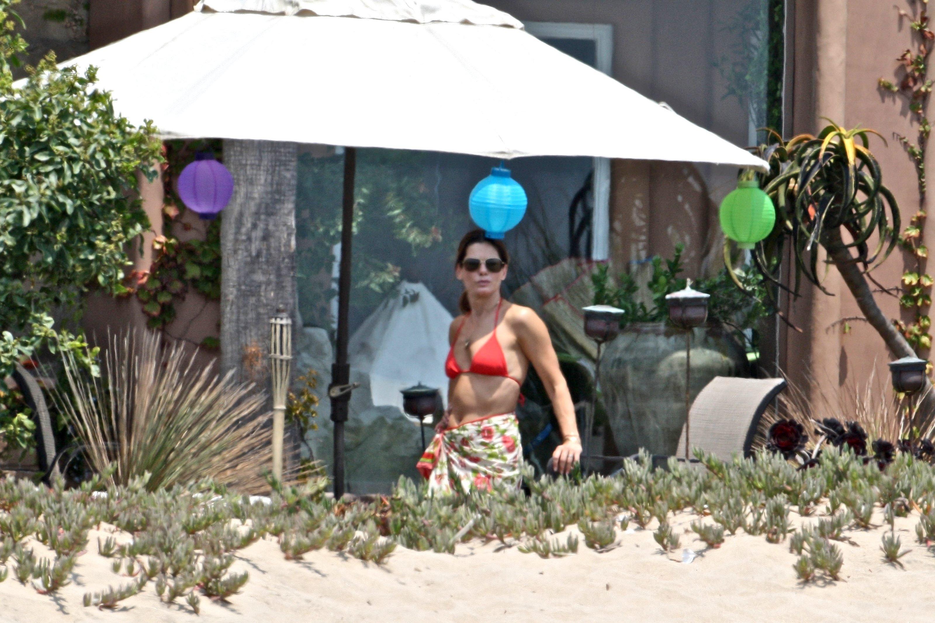 79735_Celebutopia-Sandra_Bullock_in_top_bikini_and_husband_host_an_Independence_Day_beach_party-13_122_1073lo.jpg